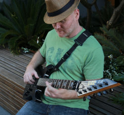 Duncan Smith playing guitar in hat looking down